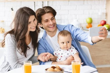 Family selfie. Millennial parents photographing themselves with baby son, dining in kitchen stock vector