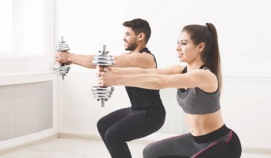 Successful couple doing squats with dumbbells and smiling
