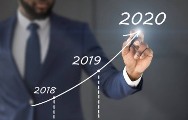 Black businessman drawing rising diagram with business strategy up to 2020