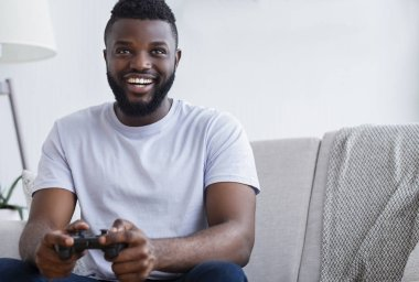 Millennial african american guy playing video games at home, holding joystick in hands, free space stock vector