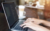 Mladá žena, která píše Java Script Code pro vytváření webových stránek