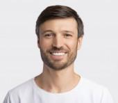 Pozitivní charismatický muž s úsměvem na kameře na bílém pozadí