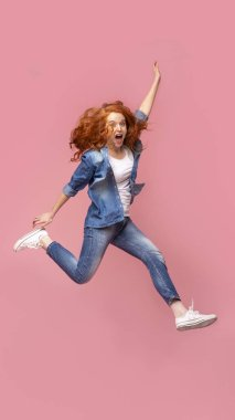 Positive redhead girl jumping over pink studio background