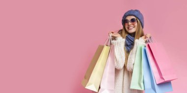 Positive girl in knitted hat and sunglasses holding shopping bags