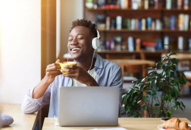 Cheerful African American guy enjoying morning coffee while listening to music in cafe, blank space