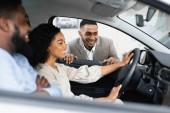 Pár Výběr nového vozidla mluvit s dealerem sedí v autě