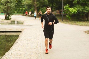Portrait of jogging guy running in modern park