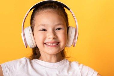 Smiling asian girl enjoying music using headphones