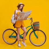 Šťastný dospívající dívka při pohledu na mapu města vedle ročníku kolo