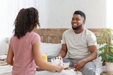 Cheerful black man looking at his girlfriend brought breakfast in bed stock vector