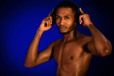 Athlete Guy Listening To Workout Music In Earphones, Blue Background