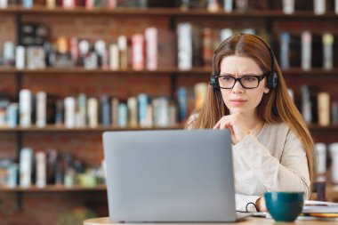 Portrait of an thoughtful young woman with headphones using laptop