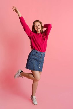 Happy teenager. Smiling girl dressed casual bouncing and dancing