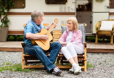 Romantic senior man playing guitar and singing song to his wife near camper van in countryside