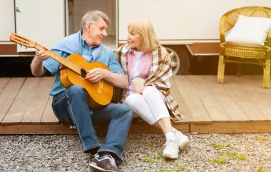 Handsome senior man with guitar performing song to his sweet wife near their recreation vehicle outdoors