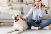 Portrait of beautiful young woman with her dog using mobile