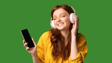 Teen Girl Enjoying Music Holding Smartphone Wearing Headphones, Green Background