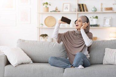 Joyful arabic girl in headphones listening music on smartphone, singing at home