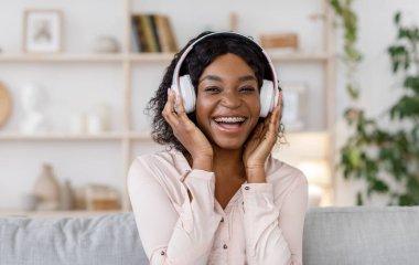 Joyful black girl with braces listening music in wireless headphones at home