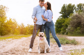 Portrait of happy young couple walking dog and kissing