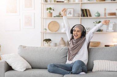 Energy Weekend. Overjoyed muslim woman listening music in wireless headphones at home