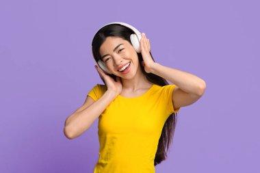 Wireless headphones for music. Portrait of asian girl enjoying listening favorite songs