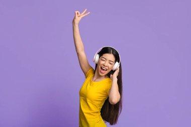Joyful asian girl in wireless headphones dancing and singing over purple background