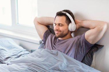 Man Listening To Music Wearing Earphones Sitting In Bed Indoors