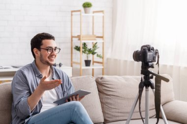 Confident young man blogger recording on camera to blog. Speaking with enthusiasm, sitting on couch stock vector