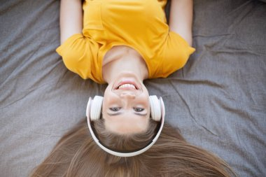 Overhead view of millennial long haired girl with headphones lying on bed, listening to music or audio book