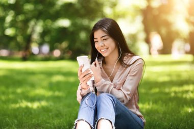 Happy asian woman listening to music on smartphone in city park