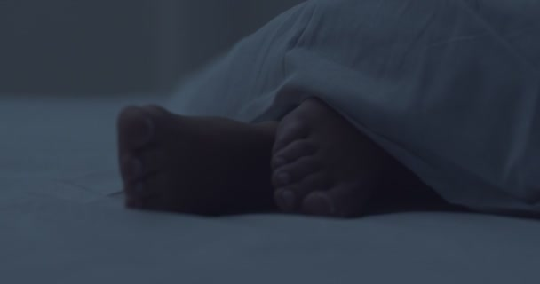 Beautiful female bare feet under white blanket, close up