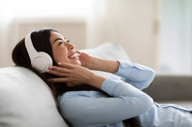 Favorite Leisure. Joyful Korean Girl Listening Music In Wireless Headphones At Home