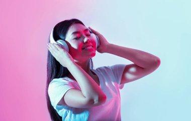 Break for music. Joyful asian girl with headphones dancing in neon