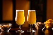 Ropogós nasi az ügyfélnek. Két pohár világos sör, chips és diófélék a bárban.