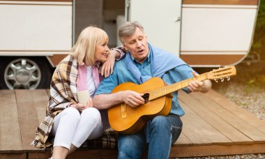 Romantic family times. Mature man singing to his charming wife near their trailer outdoors