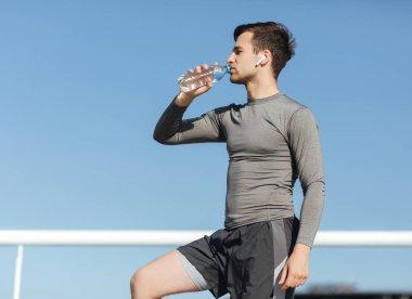 Summer workout on street. Guy in sportswear drinks water at stadium
