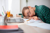 Exhausted school boy sleeping while studying at home