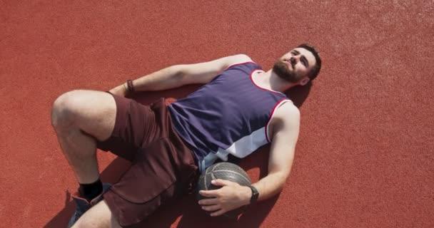 Basketbalista odpočívající po zápase, ležící s míčem na podlaze venkovního hřiště