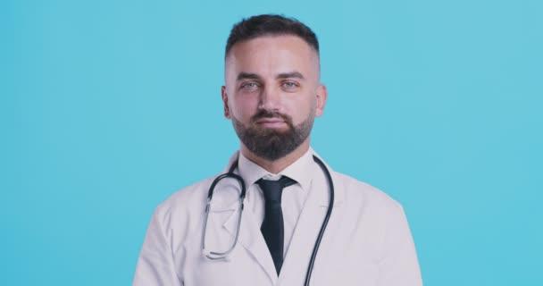 Positiver Arzt zeigt OK-Geste, blauer Studiohintergrund