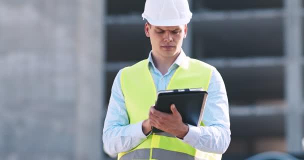 Profesionální architekt pracující s digitálním tabletem na staveništi, sledovací záběr
