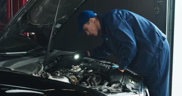 Profesionální automechanik zkoumá motor auta, hledá pod kapotou s baterkou