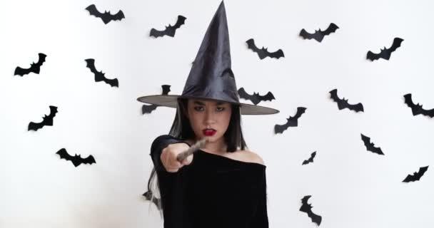 Magabiztos ázsiai nő boszorkány halloween jelmezben varázspálcával varázsol a kamera elé.
