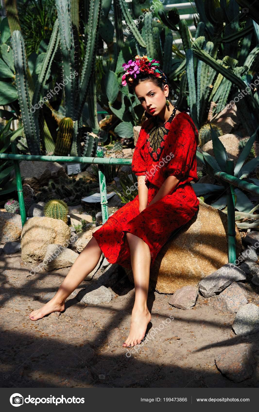 c36531818b4c Bellissima giovane donna in vestito rosso elegante e copricapo floreale–  immagine stock