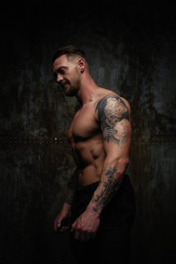 Shirtless muscled young man posing against grunge wall background