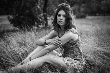 black and white photo of attractive young woman in beautiful headdress posing outdoors