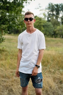 Handsome young guy in casual clothes posing outdoors