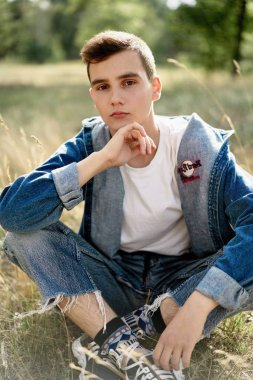 Handsome young guy in casual denim clothes posing outdoors