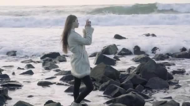 Fotografin am Ufer der stürmischen See macht Bilder. Touristenfotograf macht Bilder Ozean. stürmische See mit Gewitterwolken. Schnappschüsse einer Reise ans Meer. 4k.30fps.