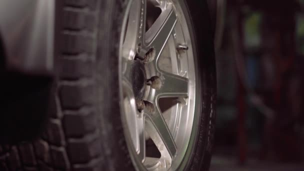Automechanik v poli garáže zpřísňuje kontroly pomocí klíč šok utáhnout auto pneumatiky nut.4k,30fps.